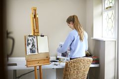 Female Teenage Artist Preparing To Draw Picture Of Dog From Photograph royalty free stock photo