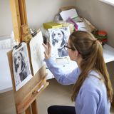 Female Teenage Artist Sitting At Easel Drawing Picture Of Dog From Photograph In Charcoal royalty free stock photo