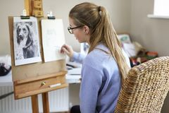 Female Teenage Artist Sitting At Easel Drawing Picture Of Dog From Photograph In Charcoal royalty free stock photos