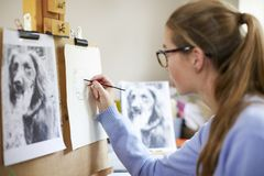 Female Teenage Artist Sitting At Easel Drawing Picture Of Dog From Photograph In Charcoal royalty free stock image