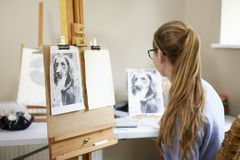 Female Teenage Artist Sitting At Easel Preparing To Draw Picture Of Dog From Photograph royalty free stock photos