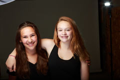 Female Teenage firends in studio. Behind the scenes studio shot of two young teenange girls posing on a grey background with lighting exposed royalty free stock photo