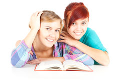 Female teenage friends reading red book Royalty Free Stock Image