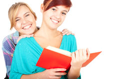 Female teenage friends reading red book Stock Photo