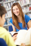 Female Teenage Student In Library Reading Book Royalty Free Stock Image