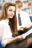 Female Teenage Student In Library Reading Book Stock Image