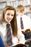 Female Teenage Student In Library Reading Book Royalty Free Stock Photography
