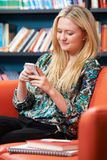 Female Teenage Student Using Mobile Phone In Library Stock Photos
