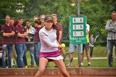 Female teenage tennis player hitting a backhand. KREMS, AUSTRIA - JUNE 16: Female teenage tennis player hitting a backhand with audience in background Stock Photography