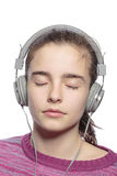 Female teenager with earphones and closed eyes. Hears music, isolated on white Stock Image