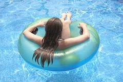 Female teenager floating on float in pool Royalty Free Stock Images
