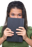 Female teenager hiding hal her face behind book. A female teenager hiding half her face behind hard cover book Royalty Free Stock Photo