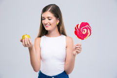 Female teenager holding apple and lollipop. Portrait of a smiling female teenager holding apple and lollipop isolated on a white background Stock Photography