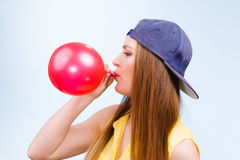Female teenager inflating red balloon. Stock Images