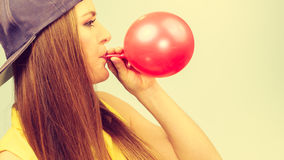 Female teenager inflating red balloon. Royalty Free Stock Photo