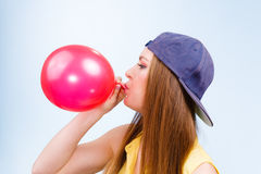 Female teenager inflating red balloon. Royalty Free Stock Image
