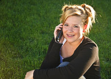 Female teenager with mobile. Portrait of smiling teenager with mobile telephone on green grass field Stock Image