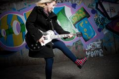 Female teenager playing guitar. Side view of trendy female teenager playing electric guitar with graffiti covered urban wall in background Stock Image