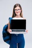 Female teenager showing blank laptop computer screen. Portrait of a smiling female teenager showing blank laptop computer screen isolated on a white background Stock Images
