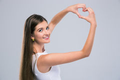 Female teenager showing heart gesture with fingers. Portrait of a happy female teenager showing heart gesture with fingers isolated on a white background stock photography