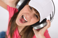 Female teenager singing with headphones Stock Images
