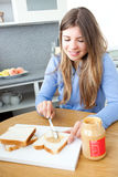 Female teenager spreading peanut butter Royalty Free Stock Photo