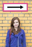 Female teenager standing under a direction sign Royalty Free Stock Images