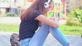 Female teenager staring at phone while seated. Female teenager staring at smart phone while seated and listening to music on white headphones stock video footage