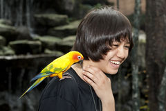 Female teenager with sun conure Stock Image