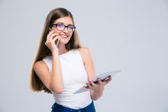 Female teenager talking on the phone and using tablet computer Stock Photos