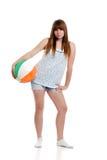 Female teenager wearing shorts holding beach ball stock photo