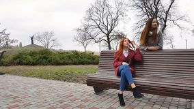 Female teenagers listening to music on smartphone at the bench. In an autumn city park stock video footage