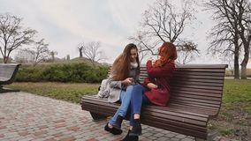 Female teenagers listening to music on smartphone sitting on the bench. In an autumn city park stock video
