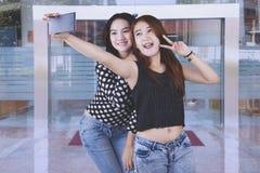 Female teenagers taking selfie in front of university front door. Cute asian female students taking selfie with peace symbol in front of university front door Stock Photography