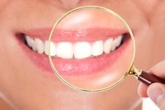 Female teeth checked with magnifying glass Royalty Free Stock Image