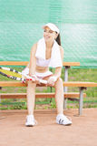 Female Tennis Athlete on Bench Resting on Tennis Court Stock Images