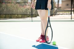 Female tennis player on base line. Low section of female tennis player standing on base line holding racket with ball on court floor, focus on legs of tennis Stock Images
