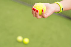 Female tennis player carrying yellow equipment Stock Image