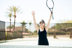 Female tennis player celebrating victory. Beautiful young female tennis player with arms raised celebrating victory on tennis court Royalty Free Stock Photo