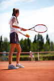 Female tennis player on court aside Royalty Free Stock Images