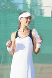 Female Tennis Player Drinking Water at Tennis Court Stock Image