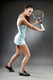Female tennis player executing a bachand volley. A full length studio shot of a female tennis player executing a backhand volley Stock Photos