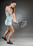 Female tennis player executing a backhand. A full length studio shot of a female tennis player executing a backhand strike Royalty Free Stock Photos