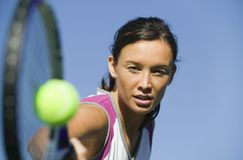 Female Tennis Player Hitting Ball close up of racket focus on player Royalty Free Stock Image
