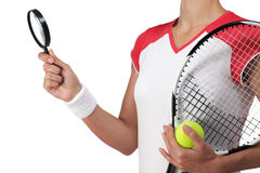 Female tennis player holding a magnifying glass Royalty Free Stock Image