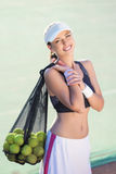Female Tennis Player Holding Many Balls in the Mesh Royalty Free Stock Photography