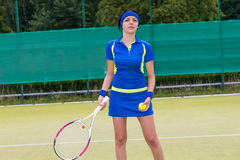 Female tennis player holding a racket and a ball on tennis court Royalty Free Stock Images