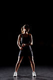 Female tennis player. Holding tennis racket and looking at distance on black Royalty Free Stock Photos