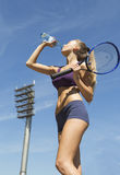 Female tennis player holds racket and drinking water Royalty Free Stock Photos