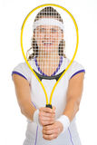 Female tennis player looking through racket Royalty Free Stock Photo